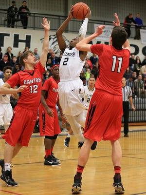 Plymouth's Randall Aikins (middle) pulls up to take a jumper over the outstretched arms of Canton's Jack Zemanski (left) during Friday's game.