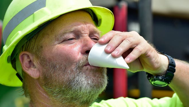 Ron Glorioso hydrates while working on a paving machine Friday, July 22, 2016 on Hades Church Road, Quincy Township. Penn DOT workers were resurfacing the area in 90 degree heat.