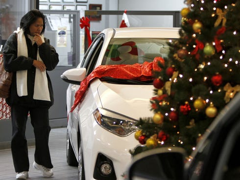 Amy Talabo, of Brownstown, Mich., looks over a 2014 Toyota Corolla while car shopping at Page Toyota in Southfield, Mich. on Dec. 12, 2013.