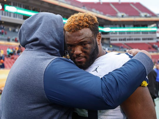 Michigan's Maurice Hurst is comforted by a teammate