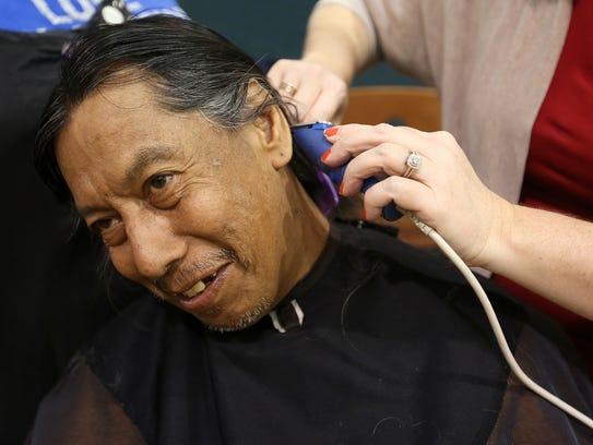 Milo Soto, 56, of Salem, has his hair trimmed by volunteer