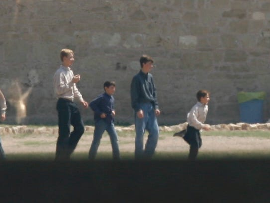 Boys from the Yearning for Zion Ranch play at Fort