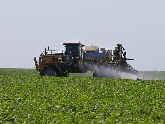 Danny Dammann sprays a soybean field in Montgomery County in July.