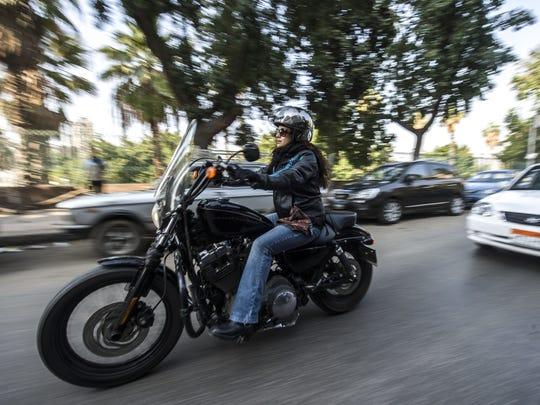 Dina Wassef rides her Harley Davidson motorbike in