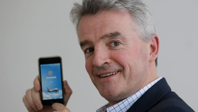 Ryanair CEO Michael O'Leary displays a new smart phone App after a press conference in London on March 26, 2014.