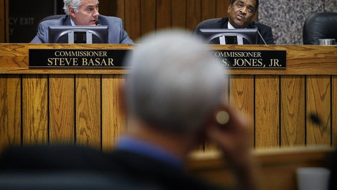 June 29, 2016 - With Shelby County Mayor Mark Luttrell (middle) listening, County Commissioners Steve Basar (left) and Eddie Jones (right) work on balancing the budget during a special called meeting of the full commission to finalize and approve a county budget before the fiscal year ends on June. 30., in the commission chambers at the Vasco A. Smith Jr. Administration Building. (Mark Weber/The Commercial Appeal)