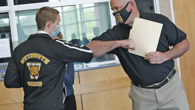 Sgt. Michael Chesna Memorial Scholarship recipient Matt Fuller, of Weymouth, gets a congratulatory elbow bump from Chesna Soccer Jamboree Director, Don Whitaker at the Weymouth Police Station on Monday.