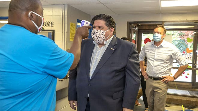 Boys and Girls Club of Decatur program director Robert Crawford checks the temperature of Gov. J.B. Pritzker before a tour on Tuesday as state Sen. Andy Manar, D-Bunker Hill, looks on.