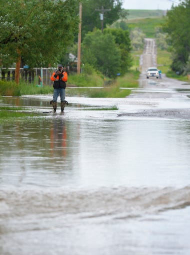 Flood water crosses Sun River-Cascade Road in the town of Sun River on Tuesday afternoon.  The Sun River is expected to crest 10.1 feet on Tuesday night.