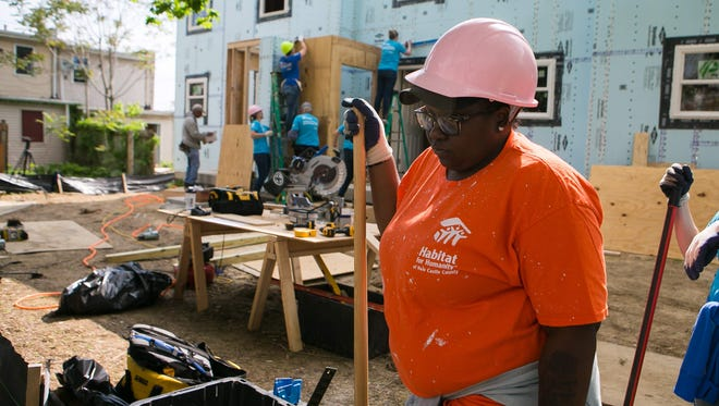 Sheniquia Brown works on the backyard fencing as local women contribute their time working alongside her future home assisting in the construction of her Habitat for Humanity home as part of the National Women Build Week.