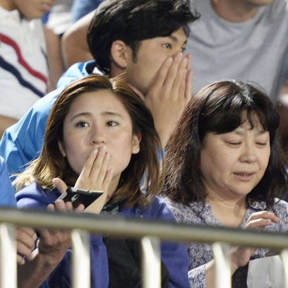Japanese soccer fans react to a strong earthquake as