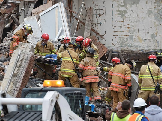 Sioux Falls Fire Rescue carries a woman to safety from the collapsed building in Sioux Falls.