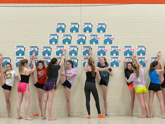 The St. Cloud Tech Tigerettes dance team goes through their wall stretching routine during practice Monday, Feb. 8, for their state tournament appearance Friday and Saturday.