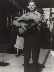 Hank Williams with a guitar on a sidewalk in Montgomery.