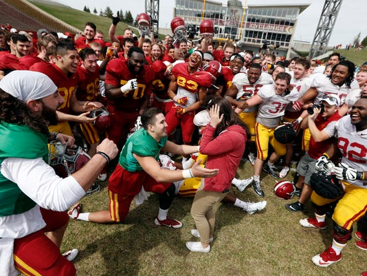 FILE - In this April 8, 2017, file photo, Iowa State quarterback Kyle Starcevich, center, proposes to his girlfriend Tori Monroe, at the end of his team's annual NCAA spring football game, in Ames, Iowa. The increasing visibility of spring football games has offered plenty of feel-good moments and fan-friendly opportunities. What they don't provide is much insight into what these teams will be doing this fall.  (AP Photo/Charlie Neibergall, File)