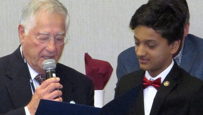 Corning Mayor Rich Negri reads a proclamation honoring national spelling bee co-champion Jairam Hathwar during Thursday's Corning Rotary Club meeting.