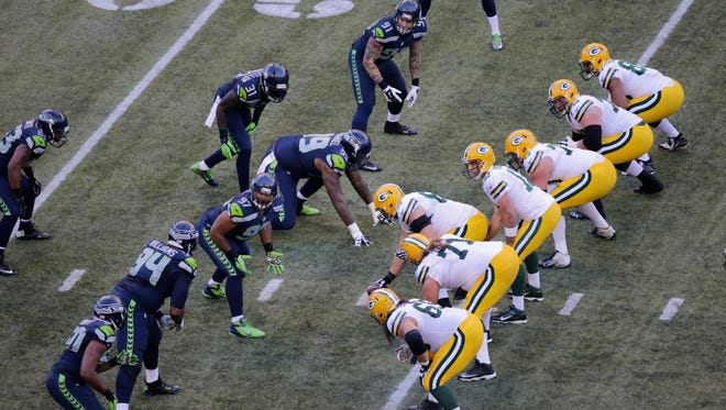 Green Bay Packers and Seattle Seahawks players line up on the line of scrimmage in the first half of the first game of the NFL season on Sept. 4 in Seattle.