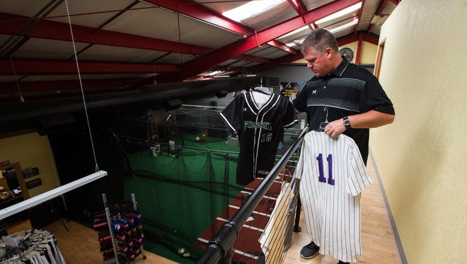 GoJo Sports owner Chris Moddelmog looks at his old Fort Collins High School baseball jersey with his daughter's current Fossil Ridge High School softball jersey on the balcony overlooking the main floor of his store, Friday.