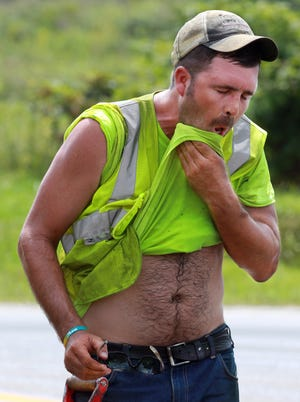 Joe Dusing, of Len Riegler Blacktop, wipes sweat from his face as he works laying asphalt on Saddlebrook Drive, Florence.