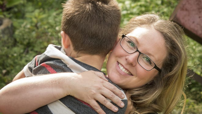 Candice Edwards hugs her 5-year-old son Oliver Charest in their Sutton yard Wednesday.