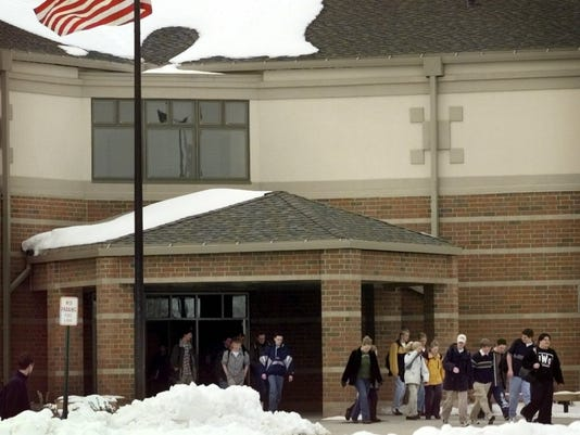 "Text: 1999.0311.01.4 digital censusmain metro In Springboro. ""Schools out"" Students at Springboro High School leave for the day as lots of snow remains on the ground from recent storms. Because of tremendous growth in Warren County, a new high school was needed in Springboro, thus the new high school on hwy. 741 just south of the small town. PHOTOS BY DICK SWAIM/CINCINNATI ENQUIRER.DS"