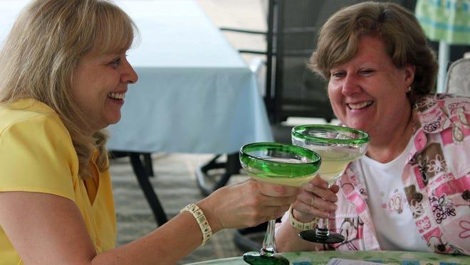 Benita Munger and Judy Palladino toast during a game night gathering in Mayfield Village, Ohio.