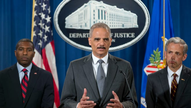 U.S. Attorney General Eric Holder, flanked by Tony West, the Justice Department's lead negotiator, left, and Colorado U.S. Attorney John Walsh, announces that Citigroup will pay $7 billion to settle a probe into subprime mortgages, the type that helped fuel the financial crisis. Holder spoke July 14 in Washington. The settlement stems from the sale of securities made of subprime mortgages, which fueled the housing boom and bust that triggered the Great Recession at the end of 2007.