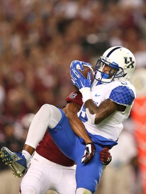 Kentucky wide receiver Garrett Johnson (9) makes catch for a first down against South Carolina's T.J. Gurley in the first half of an NCAA college football game Saturday, Sept. 12, 2015, in Columbia, S.C. (AP Photo/John Bazemore)
