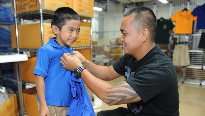 In this file photo, Noah Aguon smiles as his father Leonard Aguon checks a school uniform's fit at Gino's uniforms store at the Agana Shopping Center.