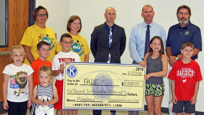 PALS members and Mary Welsh students accept a donation of $5,280 from the Williamsburg Kiwanis to be used toward new playground equipment. Shown above, back row, are PALS Vice President Angie Jensen, PALS Treasurer Angie McMullin, Williamsburg Community School District Superintendent and Kiwanis member Dr. Chad Garber, Kiwanis former president Chad Driscoll and treasurer Dave Volkens. In front, are Anna and Jillian Wiebold, Tyler McMullin, Gavin Jensen, Erica and Colby McMullin.