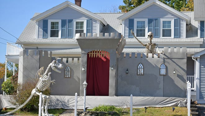 A Halloween display at 100 Oxford St. North in Auburn features a giant human skeleton looking over a castle wall and a dinosaur skeleton in the yard.