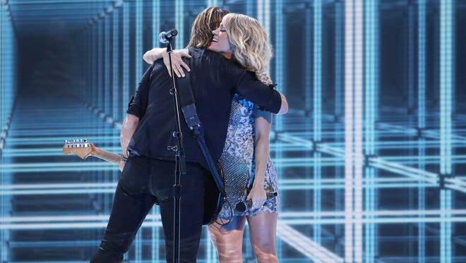 """Keith Urban, left, and Carrie Underwood embrace after a performance of """"The Fighter"""" at the 59th annual Grammy Awards on Sunday, Feb. 12, 2017, in Los Angeles. (Photo by Matt Sayles/Invision/AP)"""
