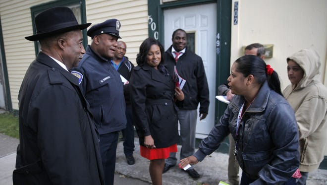 Clergy on Patrol in September 2014, with Rev. Roosevelt Dixon, left, Rochester Police School Resources Officer Moses Robinson and Mayor Lovely Warren talking with Mildred Perez, right, on Central Avenue.