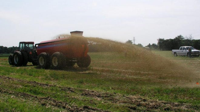 Manure is being spread via a tanker using a broadcast spray method.