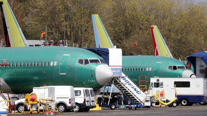 In this Monday, April 8, 2019, file photo, Boeing 737 Max 8 jets, built for American Airlines, left, and Air Canada are parked at the airport adjacent to a Boeing Co. production facility in Renton, Wash. The grounding of Boeing Co.'s 737 Max will cause a drag of about 0.2 percentage point on U.S. economic growth in the second quarter, Wells Fargo & Co. forecast on Tuesday.