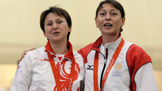 From Aug. 10, 2008, Russia's Natalia Paderina, left, and Georgia's Nino Salukvadze embrace after the women's 10 meter air pistol final at the Beijing 2008 Olympics in Beijing. Even if it takes an extra year, Salukvadze will still be aiming for an Olympic record. The Georgian shooter has competed at every Olympics since 1988, where she won a gold medal for the Soviet Union. At the Tokyo Olympics — now postponed until 2021 because of the coronavirus pandemic — she will set a women's record of nine appearances.