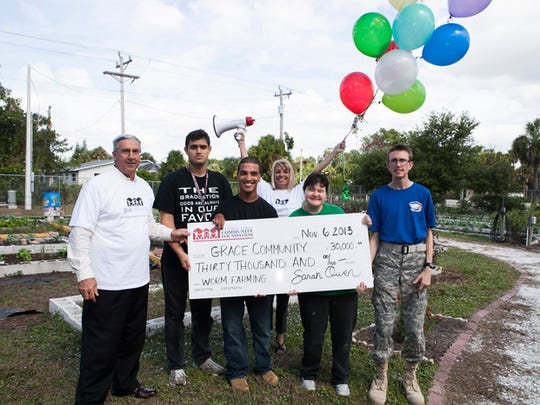"""Sarah Owen (center) calls big checks like these """"Jumbotron moments"""" that get people excited about the change the money represents."""