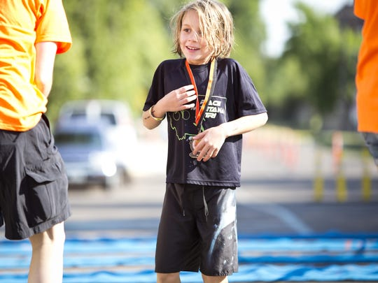 Kristian Olsen-Makdessian is awarded a medal after completing the Youth Long course at the RaceMT Triathlon at the Electric City Waterpark on Sunday, August 2.
