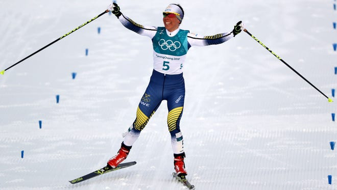 Charlotte Kalla of Sweden celebrates the win in the cross-country skiing 15K, the first medal of the Winter Olympics.