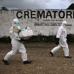 A burial team from the Liberian Ministry of Health carries soiled medical supplies to burn along with the bodies of Ebola victims in Marshall, Liberia on August 22, 2014.
