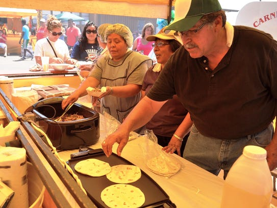 "Ignacio ""Nacho"" Meza (right) heats up tortillas during"