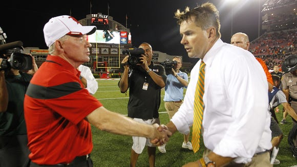 University of Louisville head coach Bobby Petrino (L) shakes hands with University of Miami head coach Al Golden (L) after winning their game 31-13 at Papa John's Cardinal Stadium in Louisville, Kentucky.       September 1, 2014