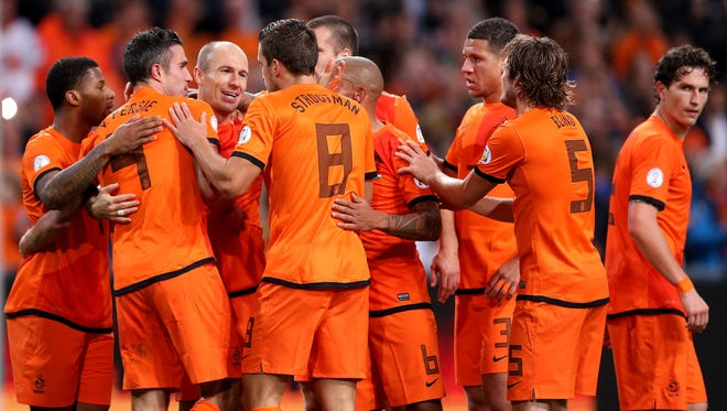 AMSTERDAM, NETHERLANDS - OCTOBER 11:  Arjen Robben of Holland (3rd L) celebrates with Robin van Persie (2nd L) during the FIFA 2014 World Cup Qualifing match between Holland and Hungary at Amsterdam Arena on October 11, 2013 in Amsterdam, Netherlands.  (Photo by Scott Heavey/Getty Images)