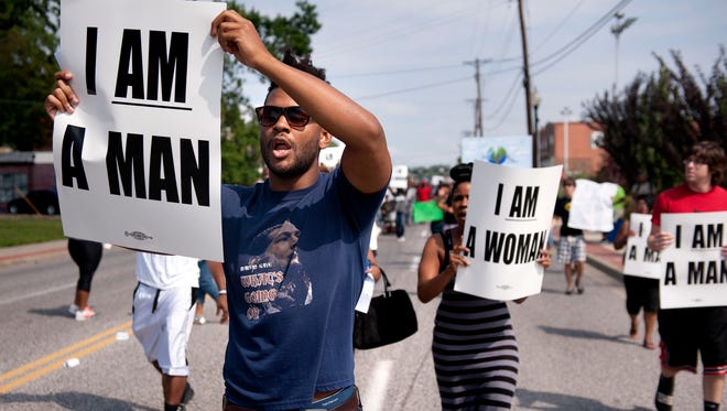 Aaron Coleman, left, joins other protesters marching in historic downtown Ferguson, Mo., Aug. 11. The group rallied in front of   police headquarters to protest the shooting of 18-year-old Michael Brown by Ferguson police.
