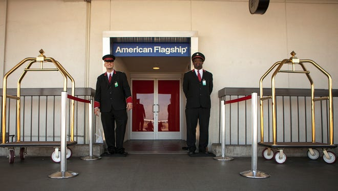 In this file photo from March 14, 2013, American Airlines skycaps Alex Abel Gonzalez, left, and Frederick Pearson await outside the AA Flagship lounge at LAX.