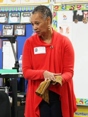 Dr. Jackie Thompson shows students at Indianola's Emerson Elementary a piece of cloth during the school's annual Culture Day March 9. Thompson told the students stories and fables passed down by various African cultures.