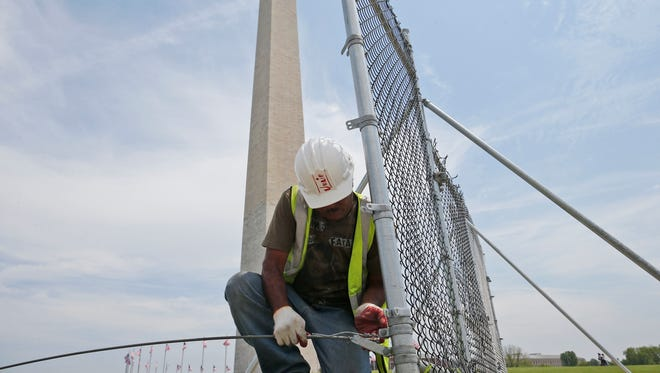 Worker Julio Dichis removes the fencing which closed the Washington Monument off to the public during renovations, Friday, May 9, 2014. The monument will be open to the public for the first time since an Aug. 23, 2011, earthquake caused extensive damage to the structure.