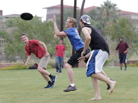University of Texas at El Paso students play a rainy game of ultimate Frisbee at Centennial Plaza on campus Tuesday.