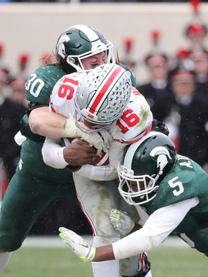 Michigan State players crunch Ohio State's J.T. Barrett during last year's game in East Lansing.