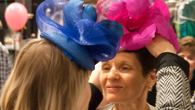 Paulette Dubofsky is helped by Jenny Pfanenstiel with a hat made by Pfanenstiel during a HerScene fashion event at Rodeo Drive boutizue.